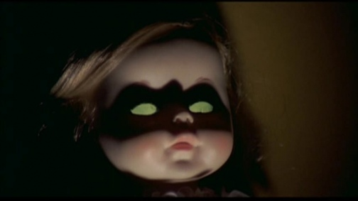 The lighting here makes the scary doll look like Batgirl. They should have just had an unnamed Batman in this movie since they were ripping off wholesale anyway.